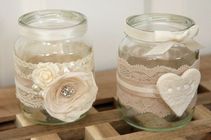 ▷1001 + Ideas for Beautiful and Ingenious Mason Jar Crafts #weckgläserdekorieren mason jar gifts, two small clear jars, with white lace, ribbons, faux flowers and a heart ornament stuck to them #weckgläserdekorieren