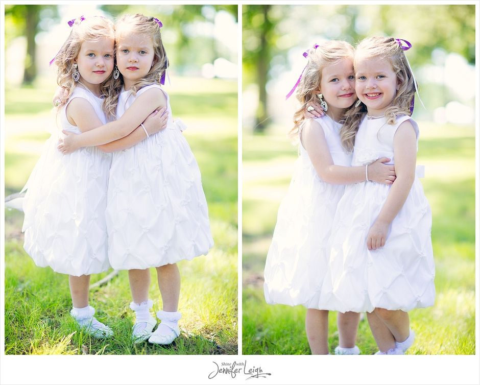 Twin flower girls dressed in white pose before the wedding