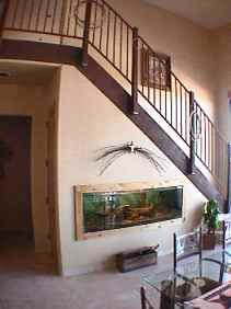 Southwest Original a SW Fish Tank under the Stairs. Rustic Dry Pine Boards Frame the SW Fish Tank. Southwest Stair Railing is Rustic Wrought Iron. Lasso Ropes hang from the SW Wrought Iron Railing as a SW Decor Detail