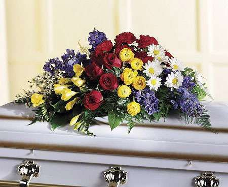 Floral oasis casket spray with bold red, blue and yellow flowers