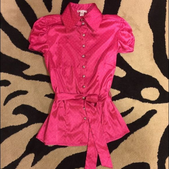 """Ambiance Apparel Satin Blouse This Satin finish blouse will surely compliment your shape whether its at work, a night out with friends, or even casually throughout the day. It has a white polkadot design with a waist cinch tie.          *Color on tag says """"cranberry"""" but is more of a bright magenta. Ambiance Apparel Tops Blouses"""