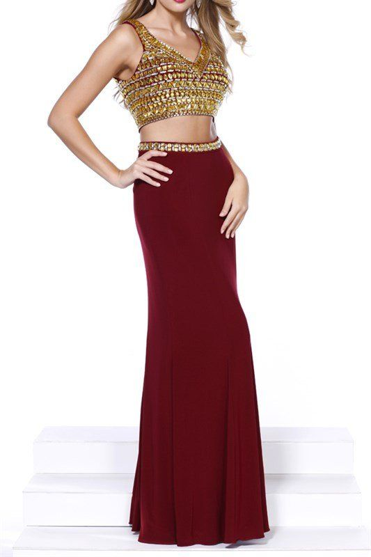 This sexy two piece dress features a fully beaded crop top that's covered in large stones to ensure you dazzle all night long! Paired with a figure hugging jersey skirt, embellished with a gold waistb