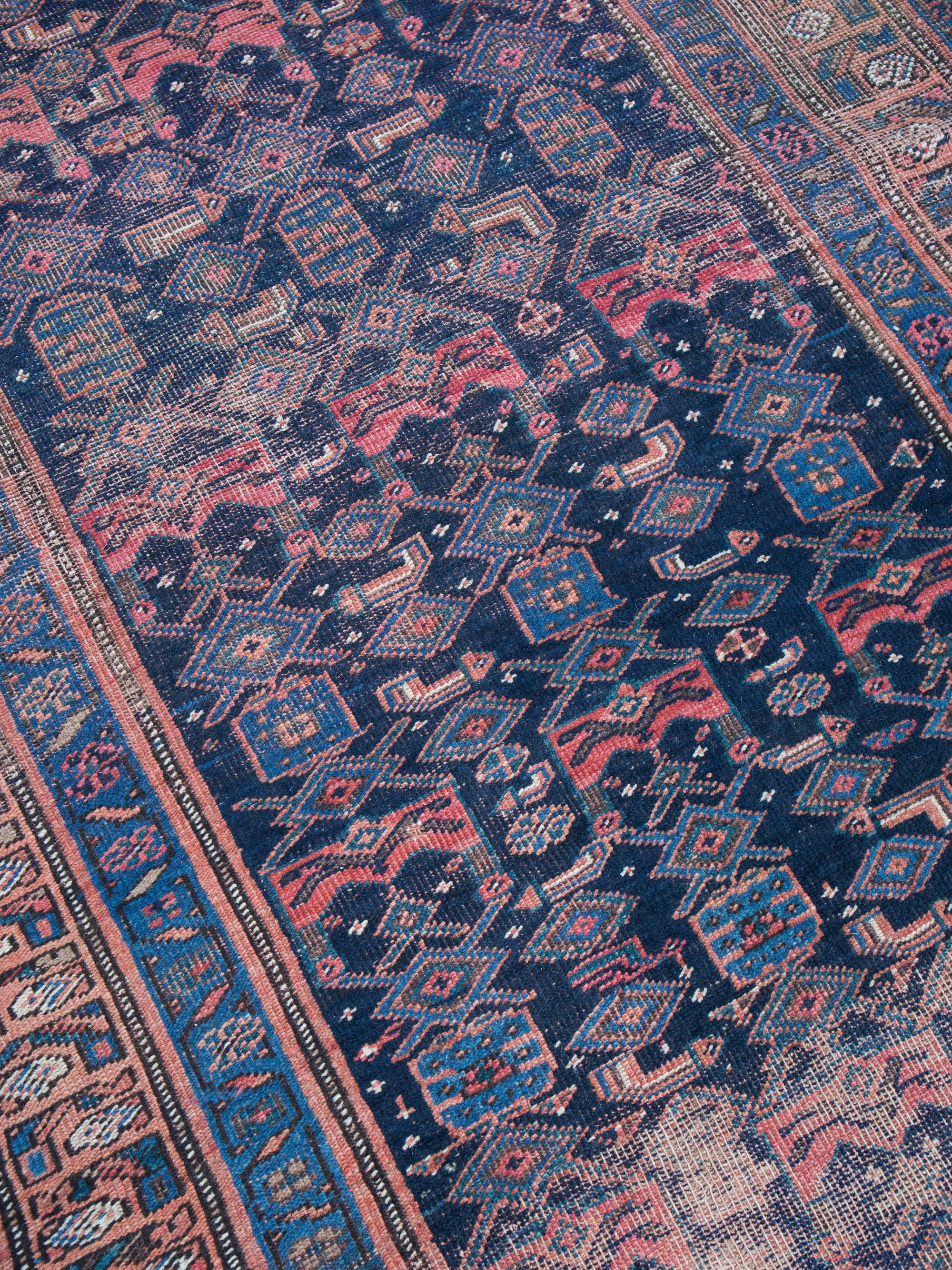 Vintage Persian rug Pile low Colors navy field red & blue accents