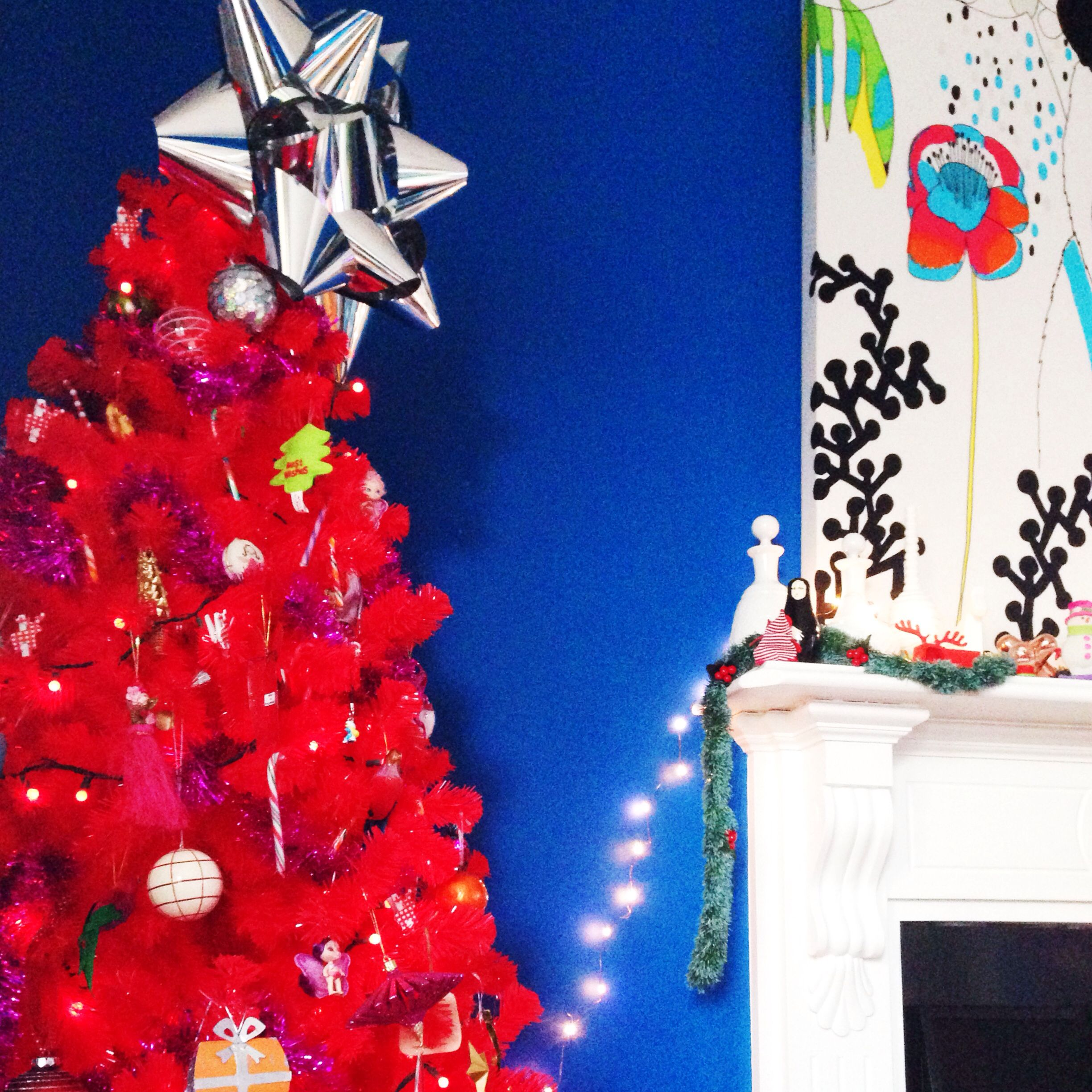 Red Christmas tree with giant bow topper in a blue room.  www.alexfultondesign.com