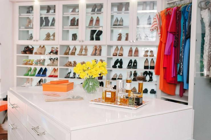 White Walk In Closet With Orange Accents Boasts An Angled Drop Down Center Island Fitted