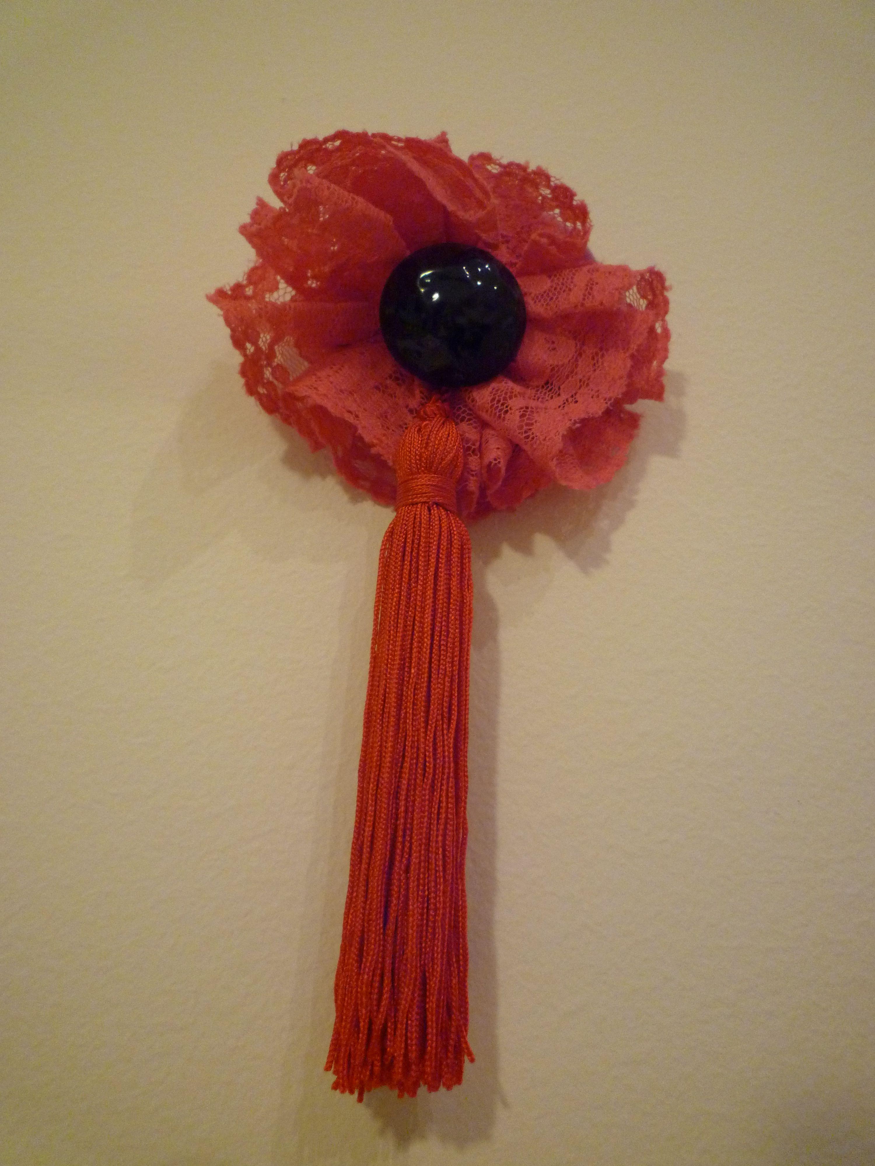 BROCHE BORLA -  Encaje rosa, borla roja y gran botón negro. Precio: € 10