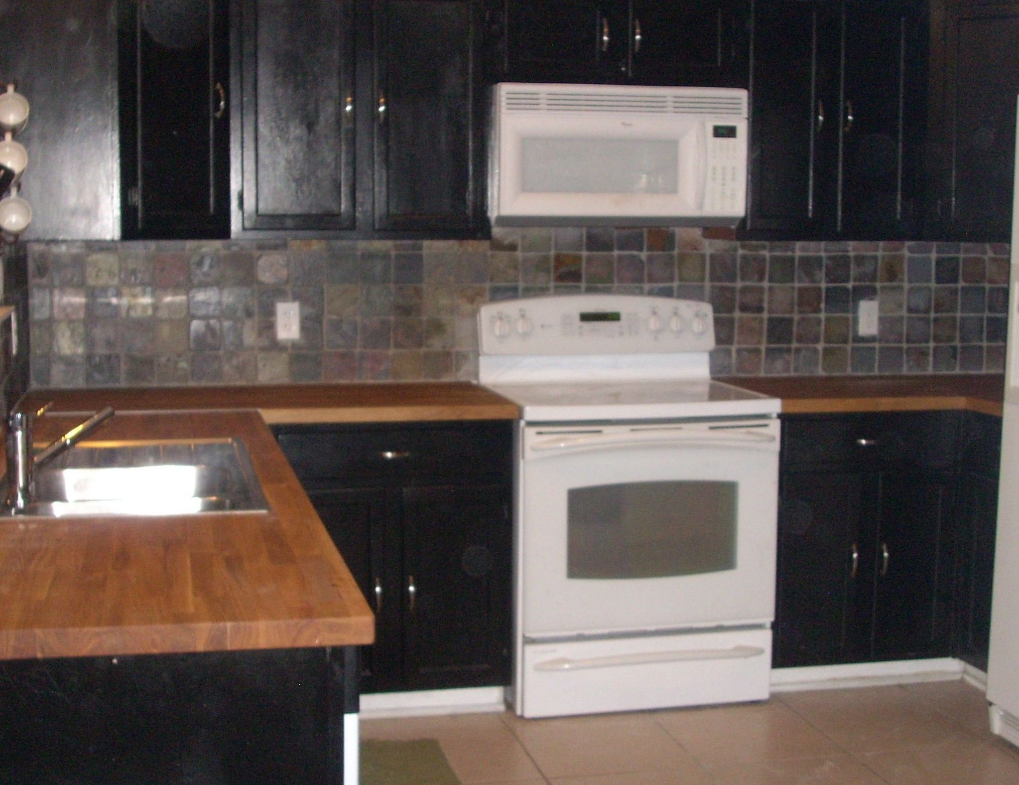 black cabinets with stainless backsplash and butcher block ...