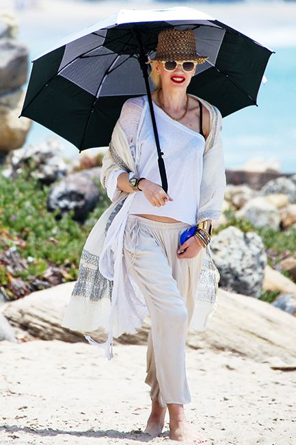 Gwen Stefani spent the day with her children on the beach in Malibu on July 13th wearing her summer whites. Stefani kept it simple in a one shoulder tee, loose pants, and embroidered scarf as she hid from the sun under with a brown patterned fedora and large umbrella to keep her skin perfect and burn-free. #largeumbrella