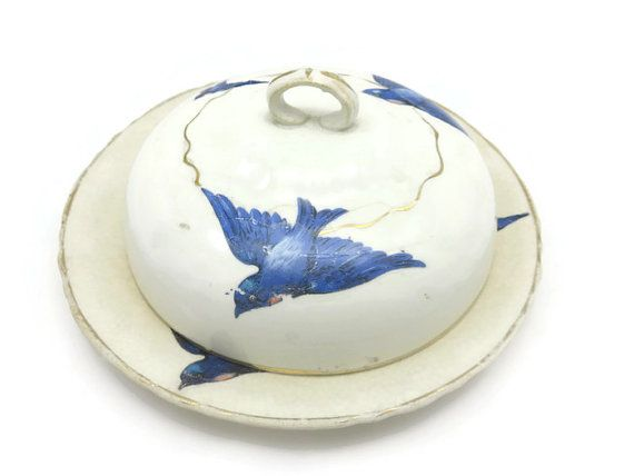 A lovely vintage porcelain covered butter dish. It includes a round plate, and a domed lid, both with flying bluebirds and gilding. Plate is