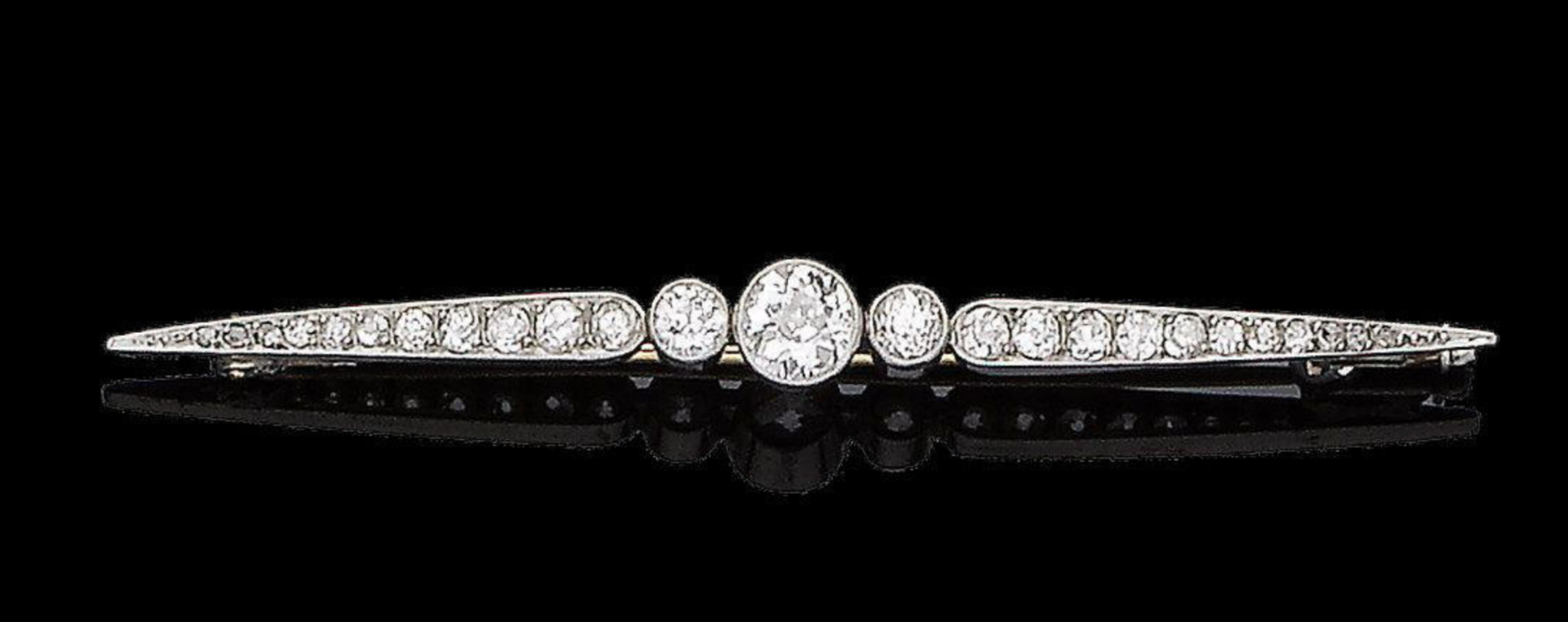 A belle époque diamond bar brooch, circa 1910 The three collet-set old brilliant-cut diamonds, the largest to the centre, between graduating similarly and rose-cut diamond shoulders, diamonds approx. 1.05cts total, length 6.5cm