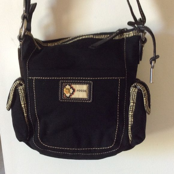 "CLOSET CLOSING.  Make me a reasonable offer. Very nice Fossil bag.  Black canvas with black/tan train. Two outside pocket with magnetic closer, pouch on front, pouch and zip pocket on back, inside pouches and zip pocket.   Zip closer.    Mesh strap changes from shoulder to crossbody.    Appro 12"" wide, 11"" tall, 4"" panel on bottom and side. 043408 Fossil Bags Crossbody Bags"