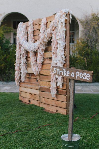 Fondo para hacer fotos en una boda a base de maderas recicladas y boas de papel.