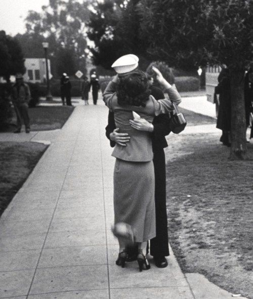 A woman embracing her husband during his graduation from Navy boot camp as her hat falls off. Photograph by Ed Clark. San Diego, California, February 1951.