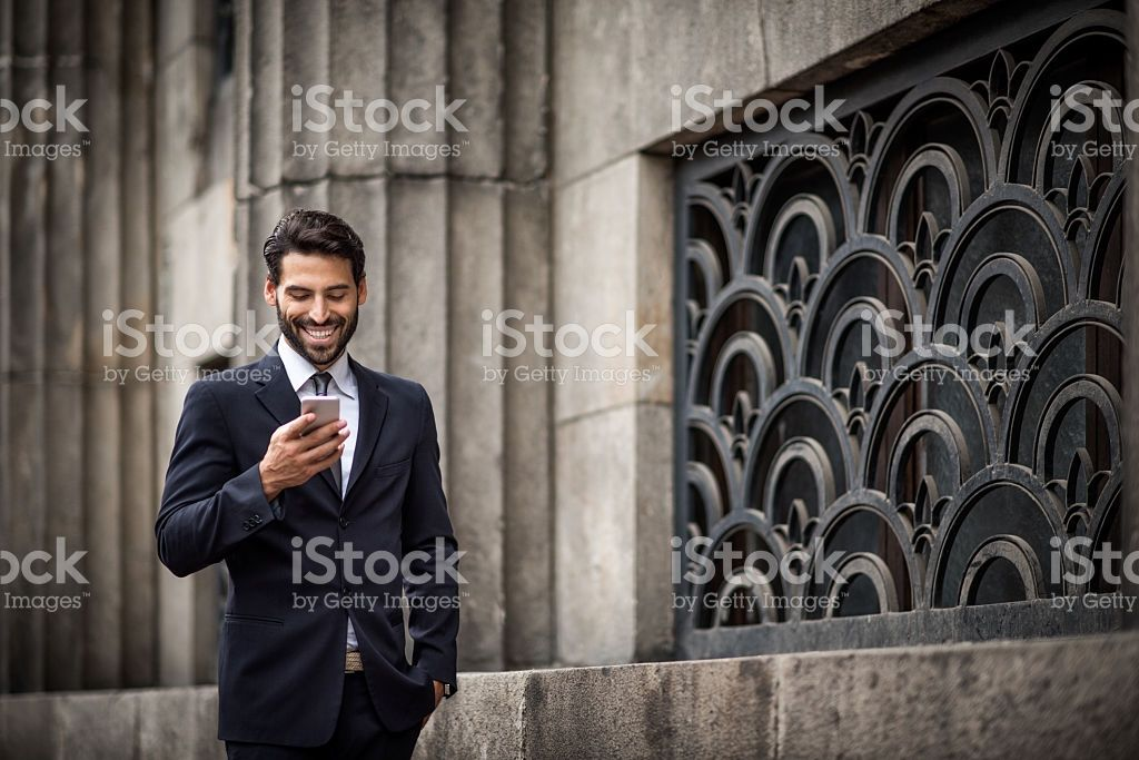 Young bearded businessman holding mobile phone and texting
