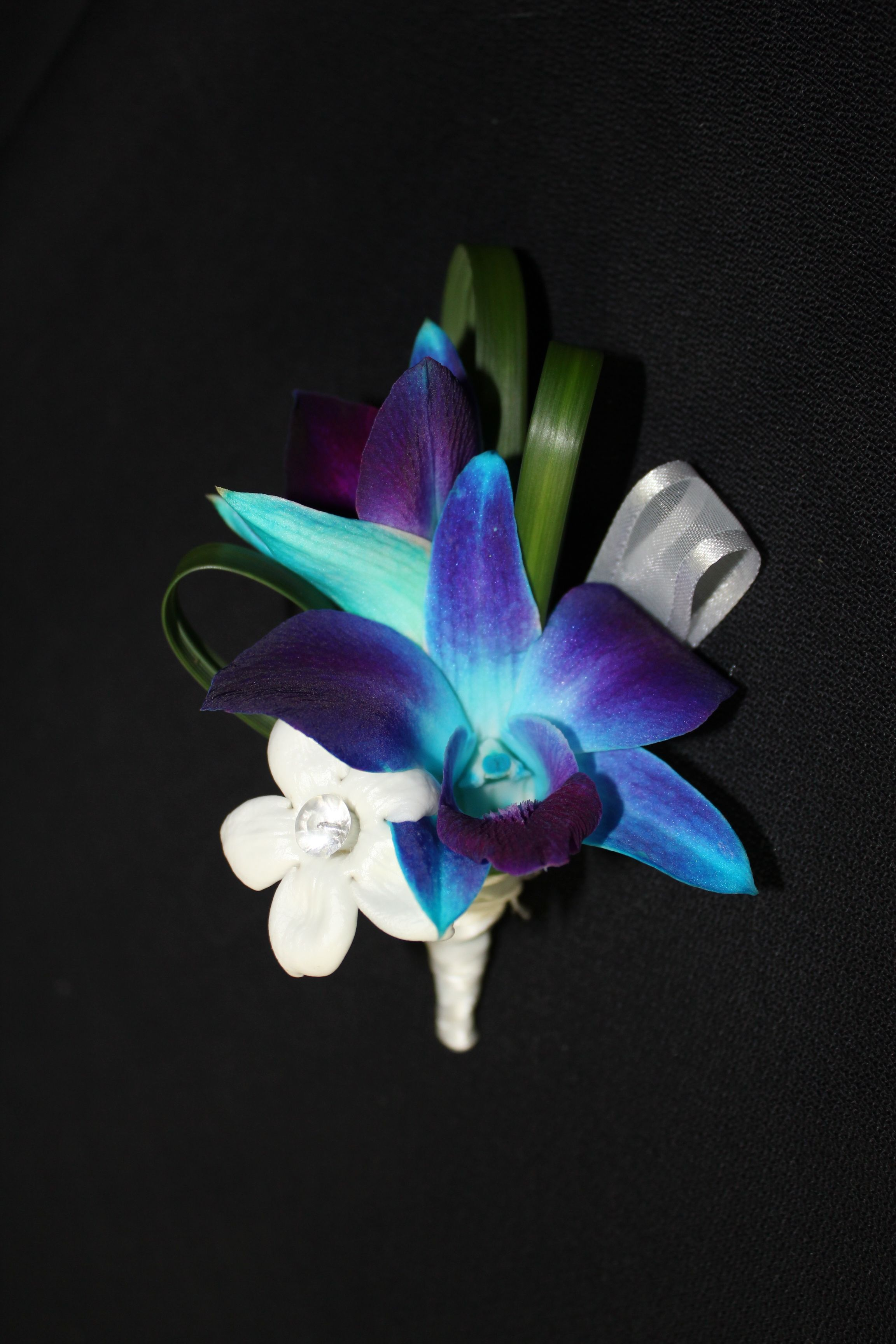 Blue dendrobium orchid and white stephanotis boutonnierre with lily