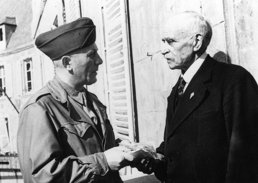 """Le maire de Cherbourg Paul Renault (jusqu'au 1 octobre 1944) accepte les recettes du cinéma pour les oeuvres de charité.  Photo prise sur le balcon de l'Hôtel de Ville.  Le soldat américain porte l'Insigna Collar """"US"""" sur son col de chemise"""