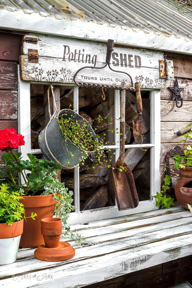 Rustic shed reveal with sawhorse potting bench and old rake sign for garden tools