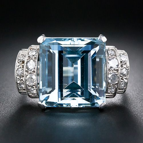 An entrancing and highly saturated, pastel blue, square emerald-cut Aquamarine - weighing 12.50 carats - glistens brightly from a beautifully sculpted platinum and diamond ring displaying classic Art Deco architectural geometry. The shoulders of the ring sparkle with gently curved diamond steps and the side gallery displays graceful decorative open work. This sizable, fun and refreshing bauble from the 1930s measures one inch across by 9/16 inch from top to bottom.