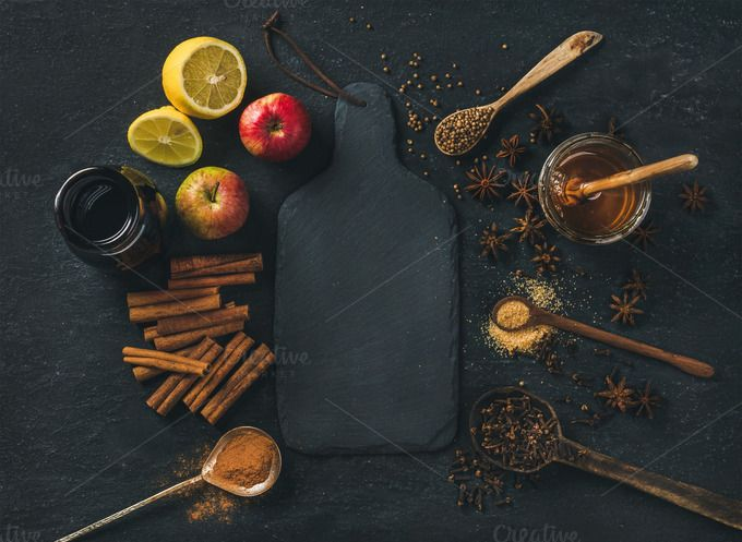 #Ingredients for making mulled wine  Ingredients for making mulled wine. Wine in glass bottle honey lemon apples and spices over black slate stone background with board in center top view copy space