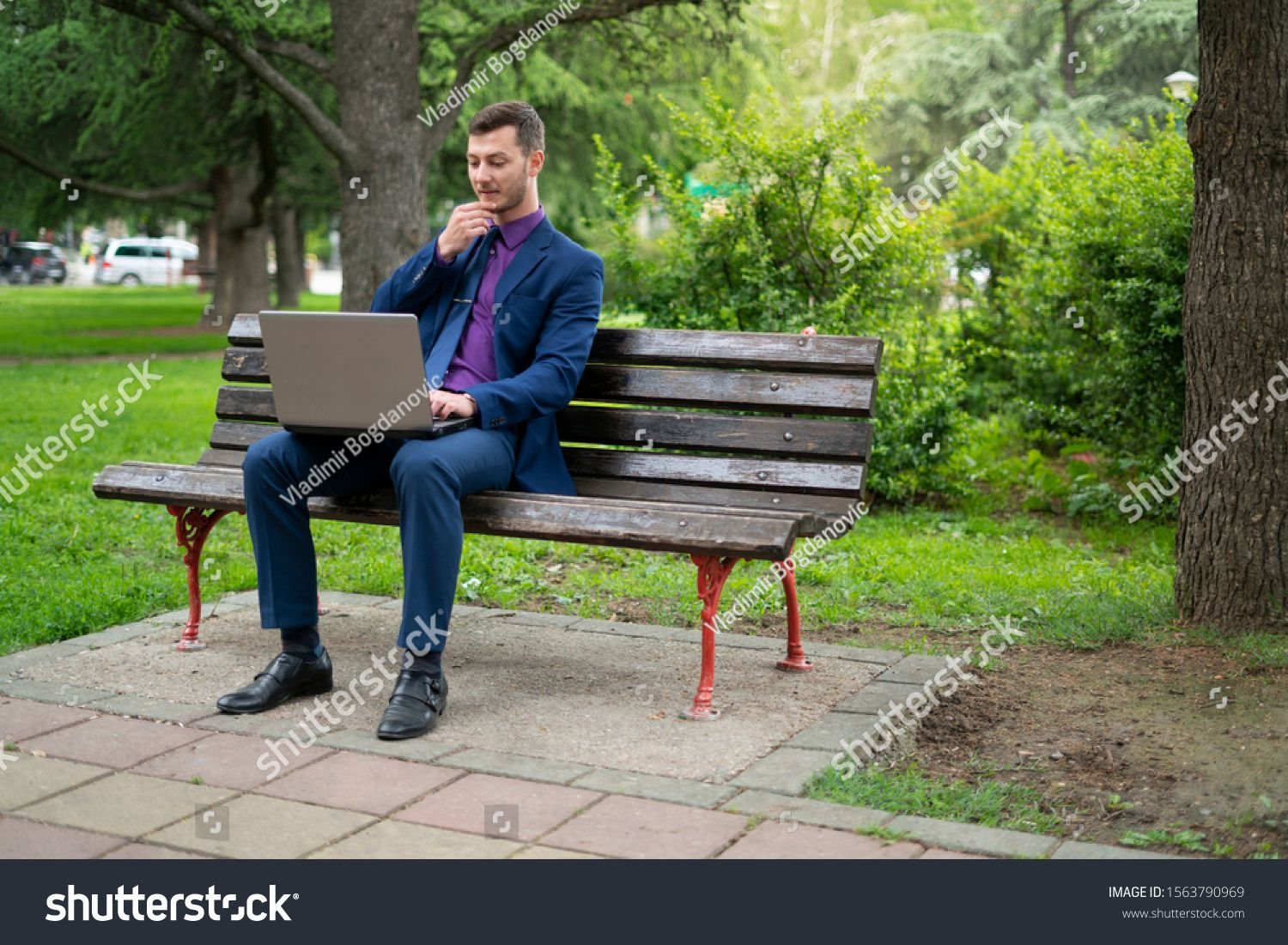 Young Businessman In Blue Suit Is Sitting On Park S Bench And Working On His Lap Top He Si Making An Important Business Deci Blue Suit Business Man Park Bench