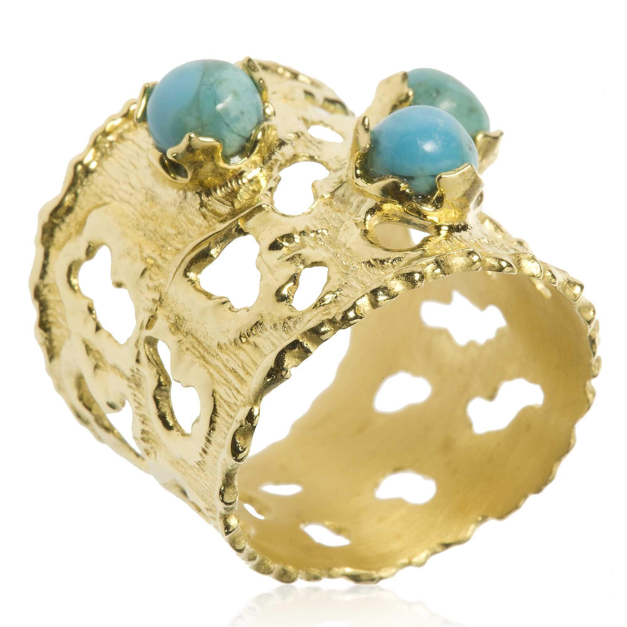 Etrusca, anello a fascia in bronzo placcato oro giallo. Ha il bordo irregolare ed una finitura satinata, a corteccia, su cui si inseriscono tre turchesi cabochon. Attingi al fascino della gioielleria antica, per un look inaspettatamente nuovo.
