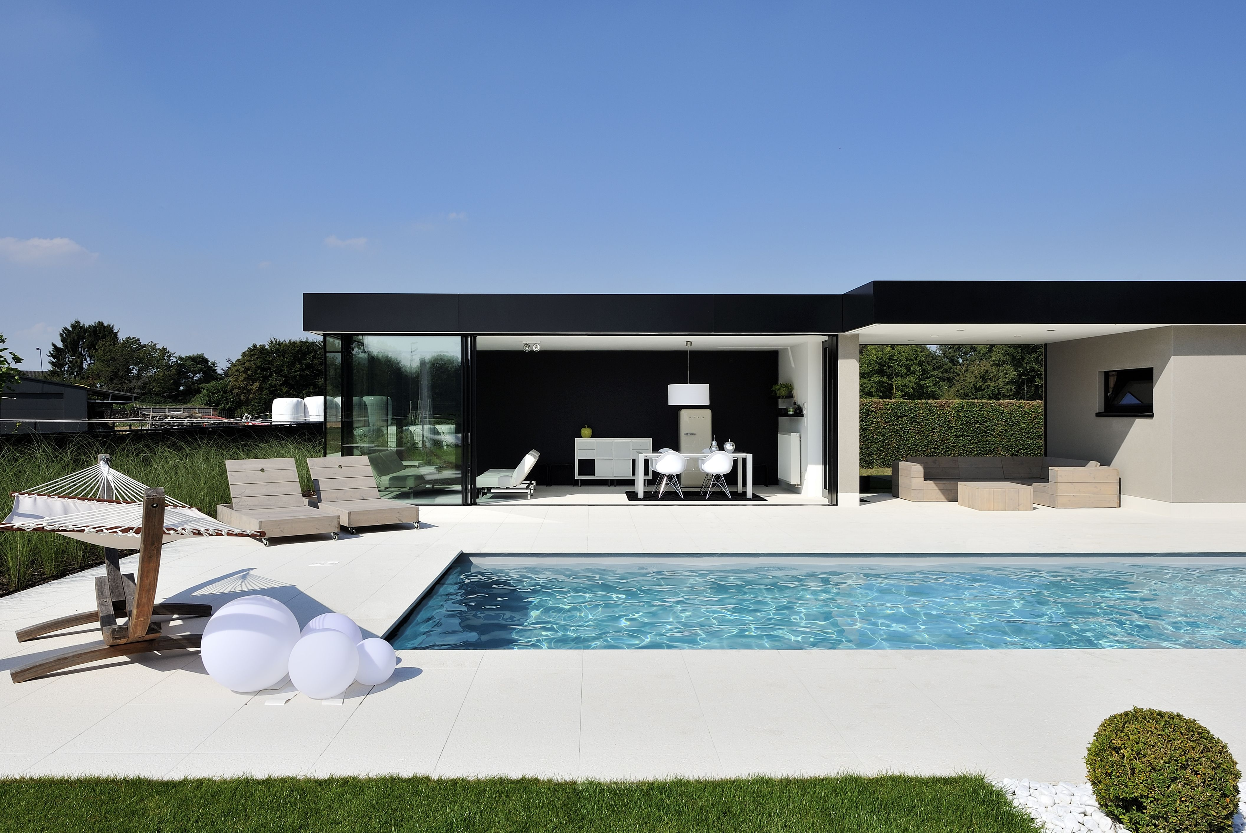 sliding minimal windows to a modern pool side living room, the