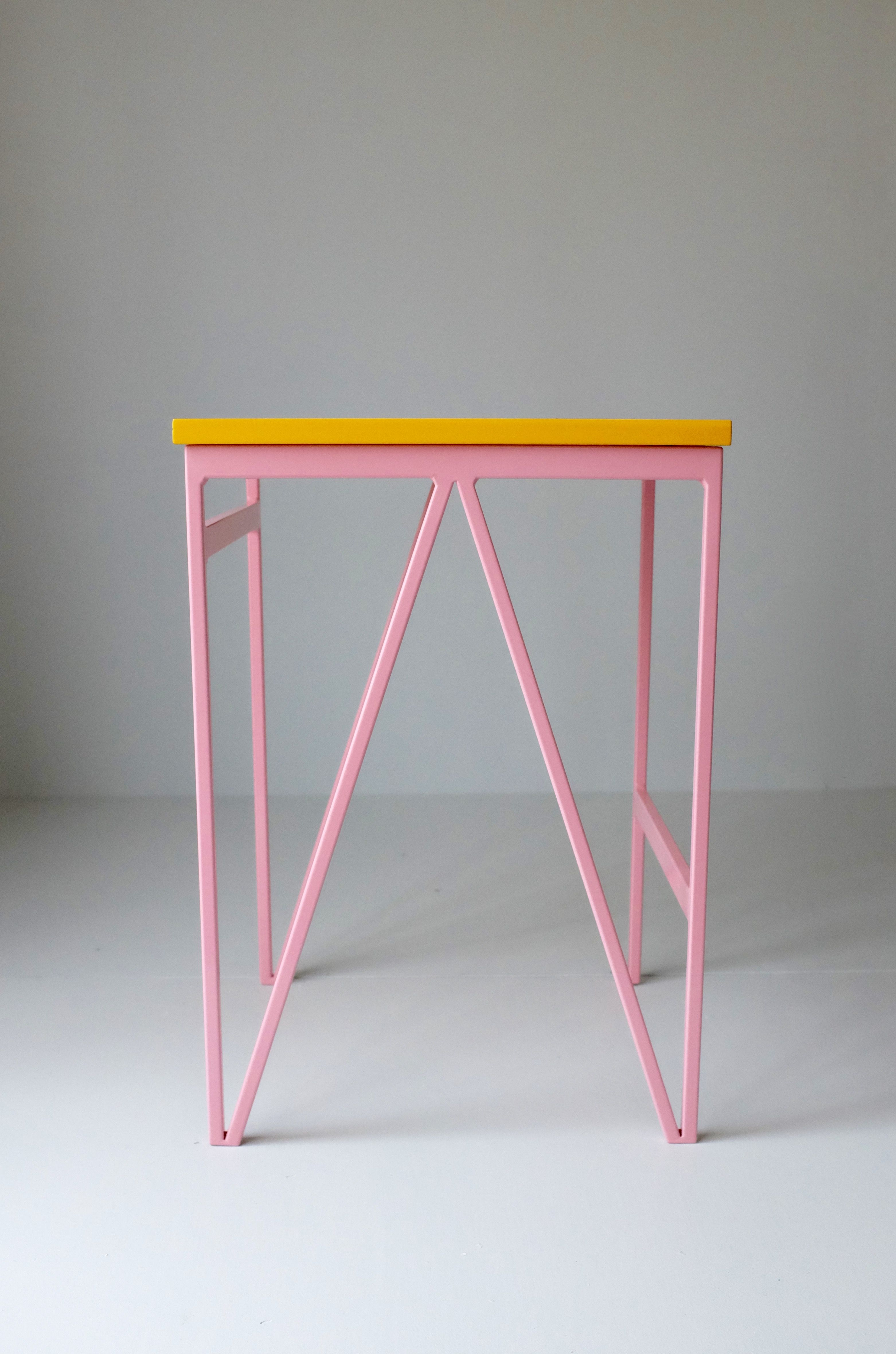 Pink powder coated steel frame and yellow colour lacquered plywood top minimal modernbritishfurniture powdercoatedsteel stool