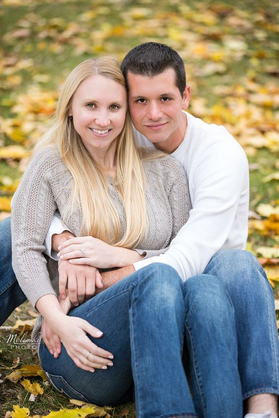 A couple sitting amongst fall leaves. Copyright Photographics Solution 2013