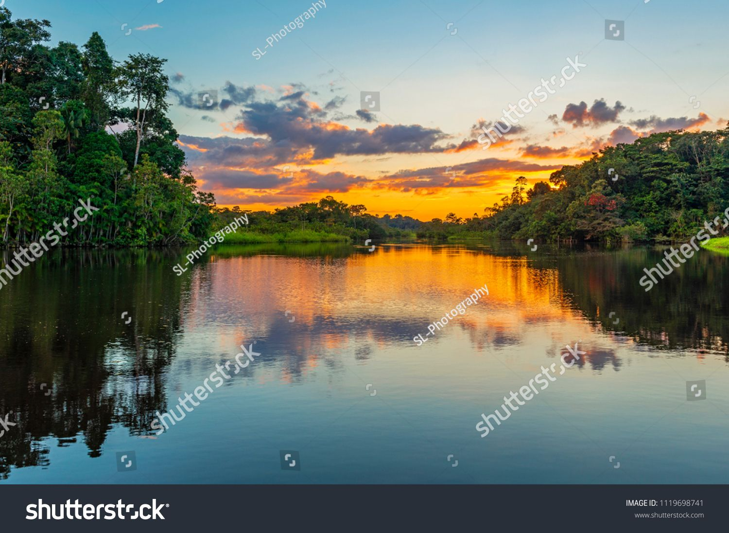 Reflection Of A Sunset By A Lagoon Inside The Amazon Rainforest