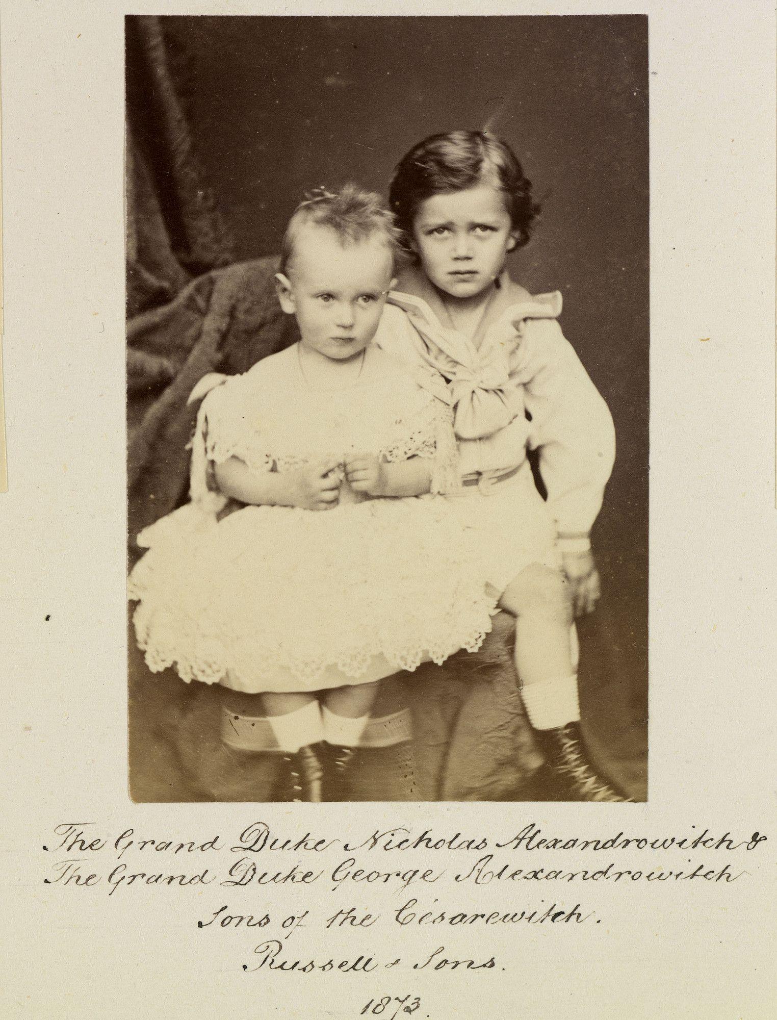Grão-duque Nicolau Alexandrovich, mais tarde, Nicolau II, e Grão-Duque George Alexandrovich. Os dois meninos estão sentados lado a lado com o Grão-Duque George Alexandrovich à esquerda usando um vestido. Em 1873.