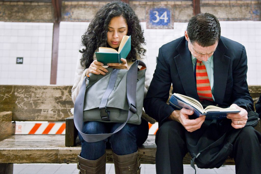 "Underground New York Library  |  Commuters reading: Left - Pablo Neruda poetry. Right - ""Time Travel and Warp Drives"""