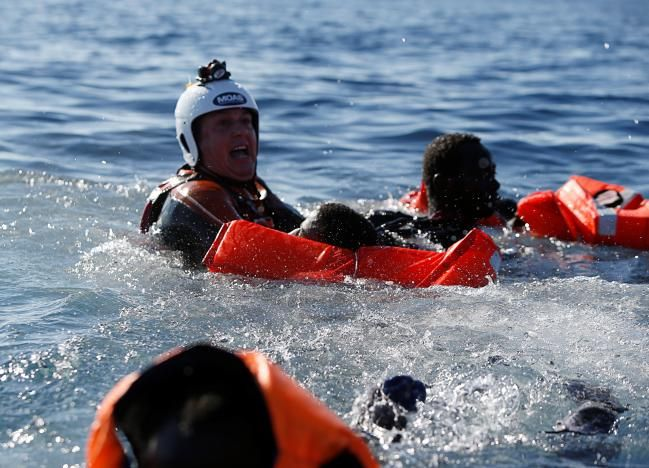 More than 2,000 migrants trying to reach Europe were plucked from the Mediterranean on Friday in a series of dramatic rescues and one person was found dead, officials and witnesses said.