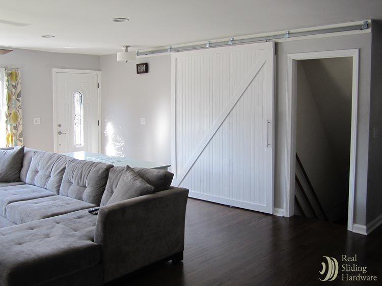 Sliding barn door alternately covers laundry openings for Basement sliding doors