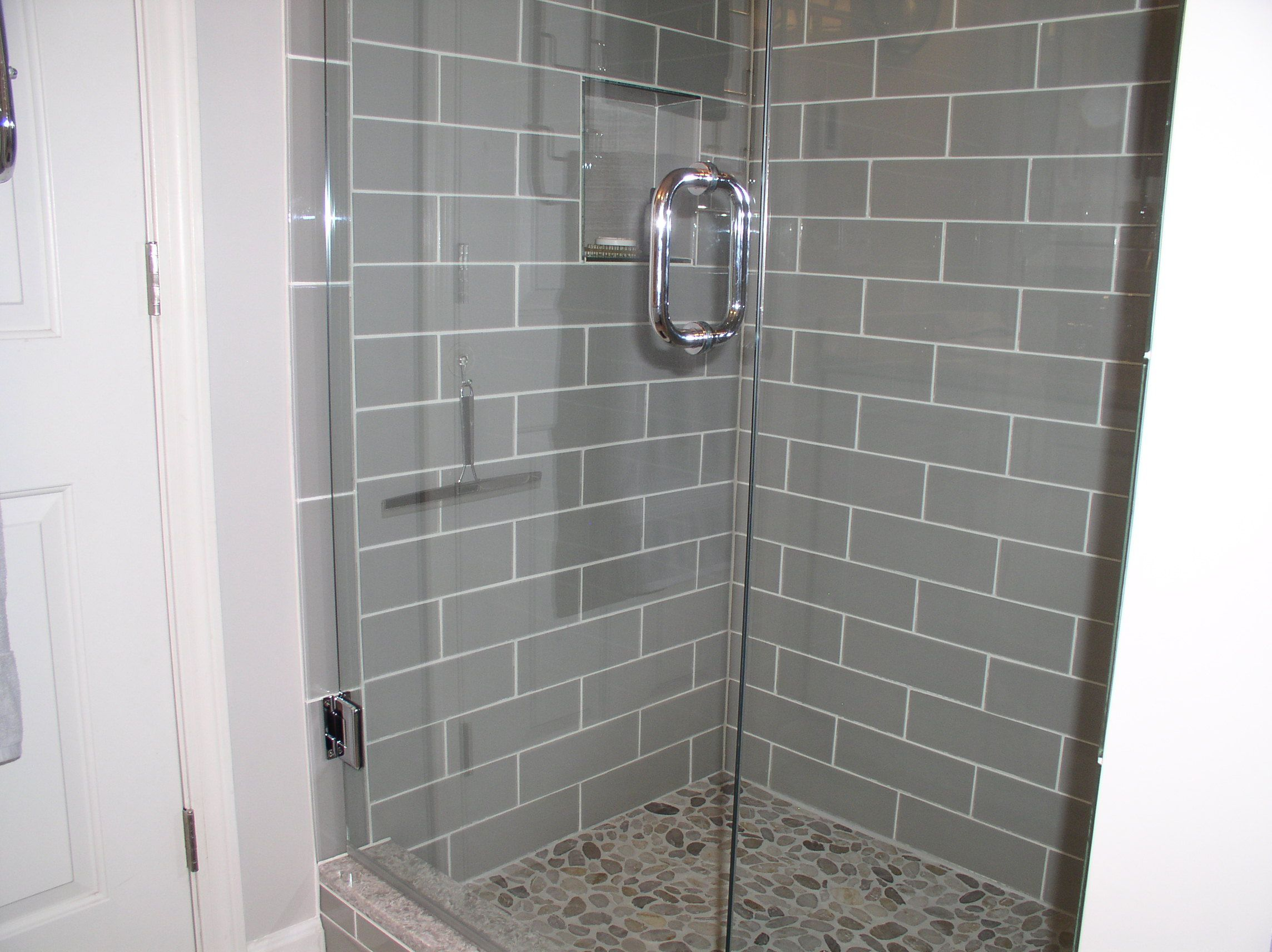 Smoke glass 4 x 12 shower walls with our sliced pebble tile on the