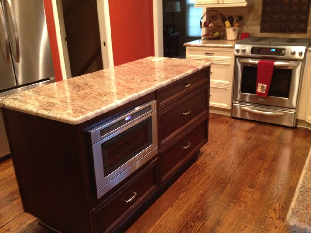 Microwave In Island With Dark Cabinetry With Light Granite