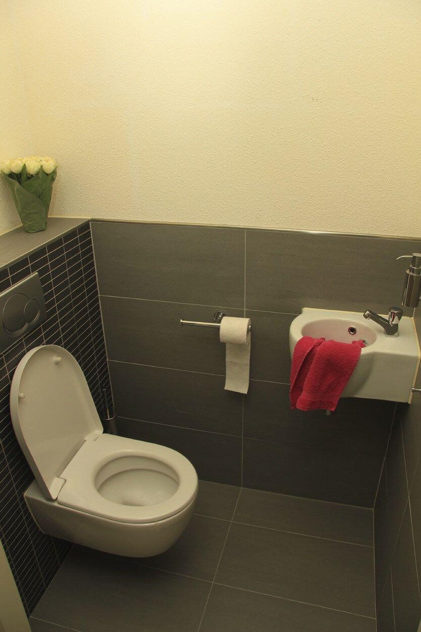Black And Gray Tiled Half Bathroom With Storage Shelf