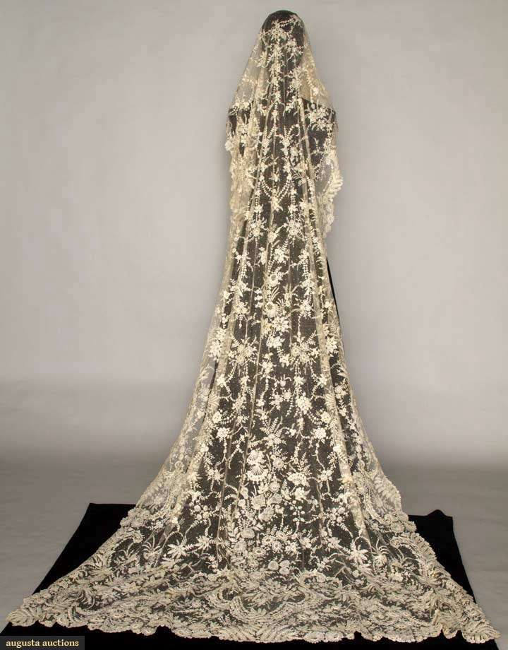 """BRUSSELS MIXED LACE WEDDING VEIL, 1860-1870 Handmade toile & reseau, edging of small flower vines, scrolls & scallops, some w/ needle lace fillings, oval veil crown w/ point d'espirit, veil narrows near top, wider towards bottom w/ squared corners, Bottom W 53"""", L 108"""", (minor light stains near crown, few other small stains) excellent. Estate of Marion Powys, renowned early 20th C lace expert & owner of Devonshire Lace Shop, 556 Madison Ave, NYC, 1916-1948..$5700."""