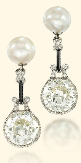 *EARLY 20TH CENTURY DIAMOND AND NATURAL PEARL EAR PENDANTS / Each designed as a circular-cut diamond weighing 7.23 and 6.64 carats to the natural pearl surmount, with onyx and diamond connecting links, Circa 1920.