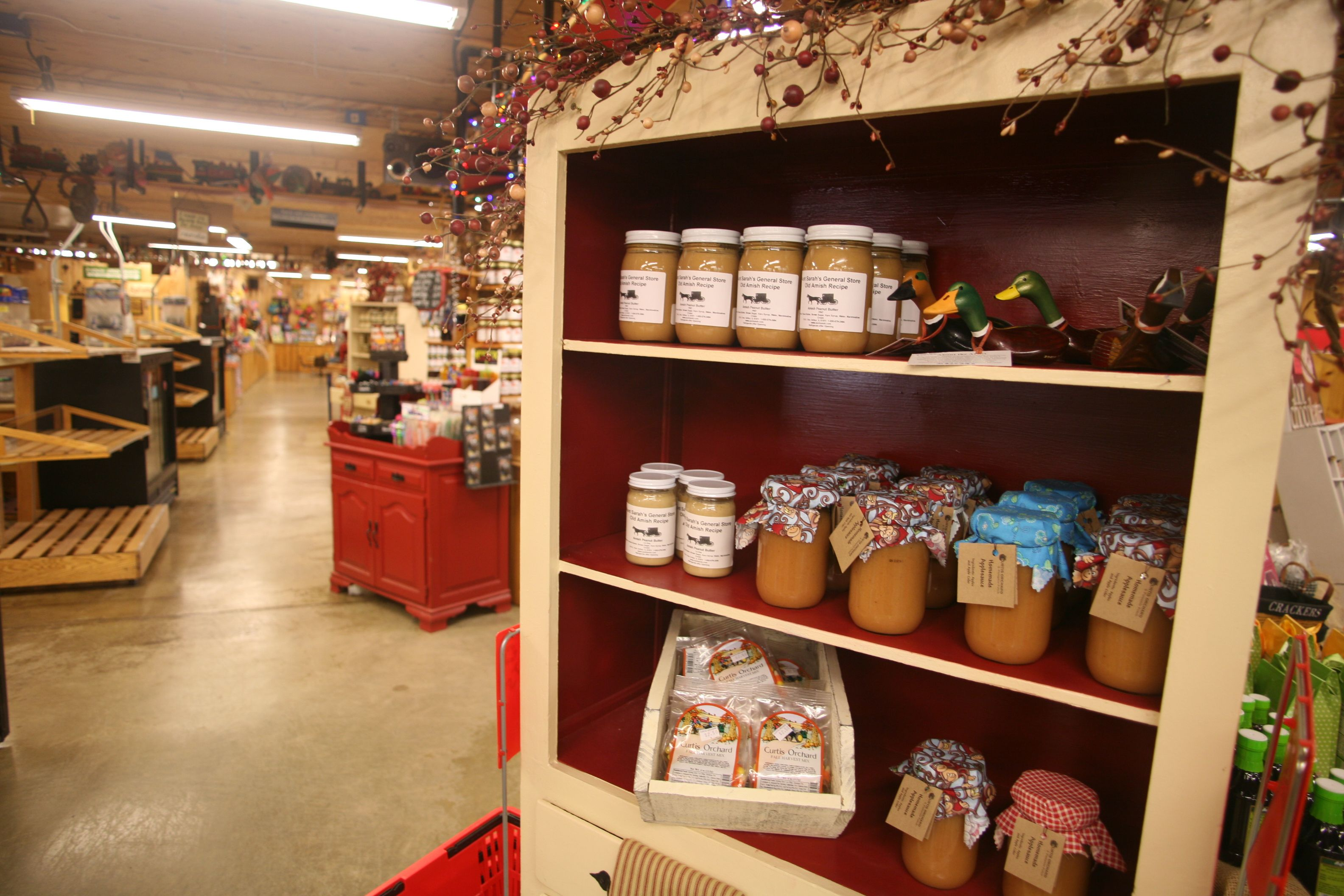 Jars Of Apple Sauce Are Appealingly Accented When Set Against A Rich Red Background A Garland Of Berries Provides Add Champaign Display Cabinet Store Displays