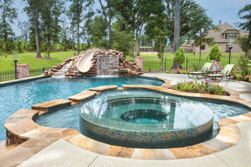 Infinity Edge Hot Tub Surrounded By Tanning Ledge Freeform Pools Pool Builders Hot Tub