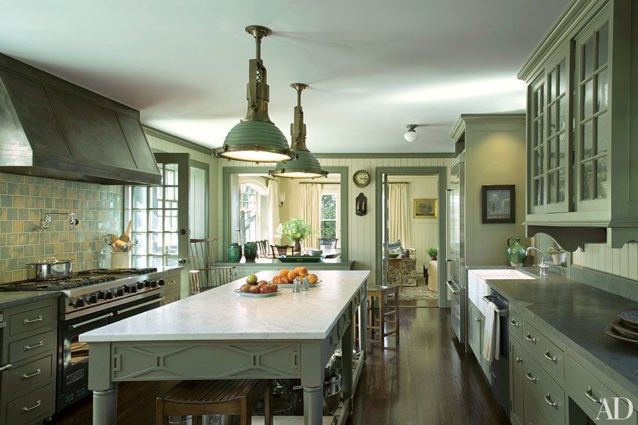Green cabinetry and a pair of pendant ceiling lights add a ...