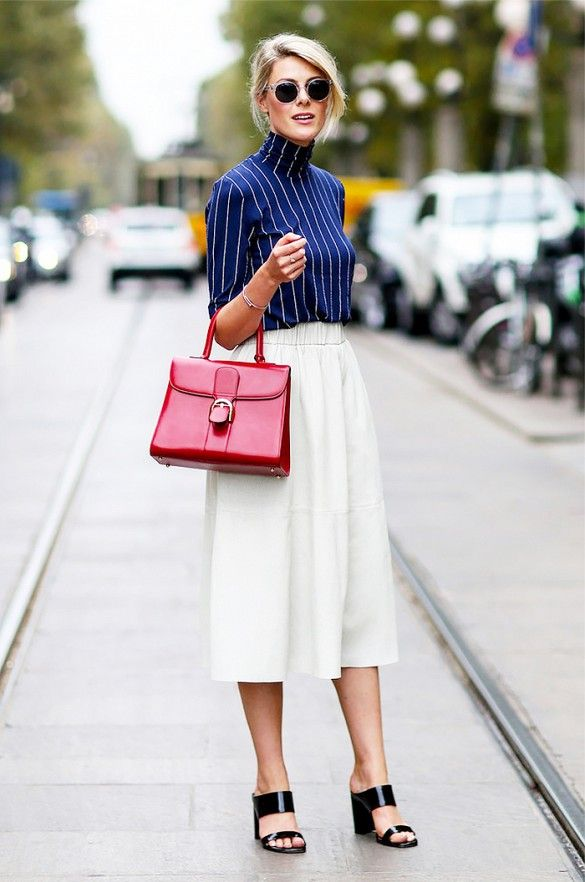 A blue pinstripe turtleneck is paired with a white midi skirt, mules, and a red top handle bag