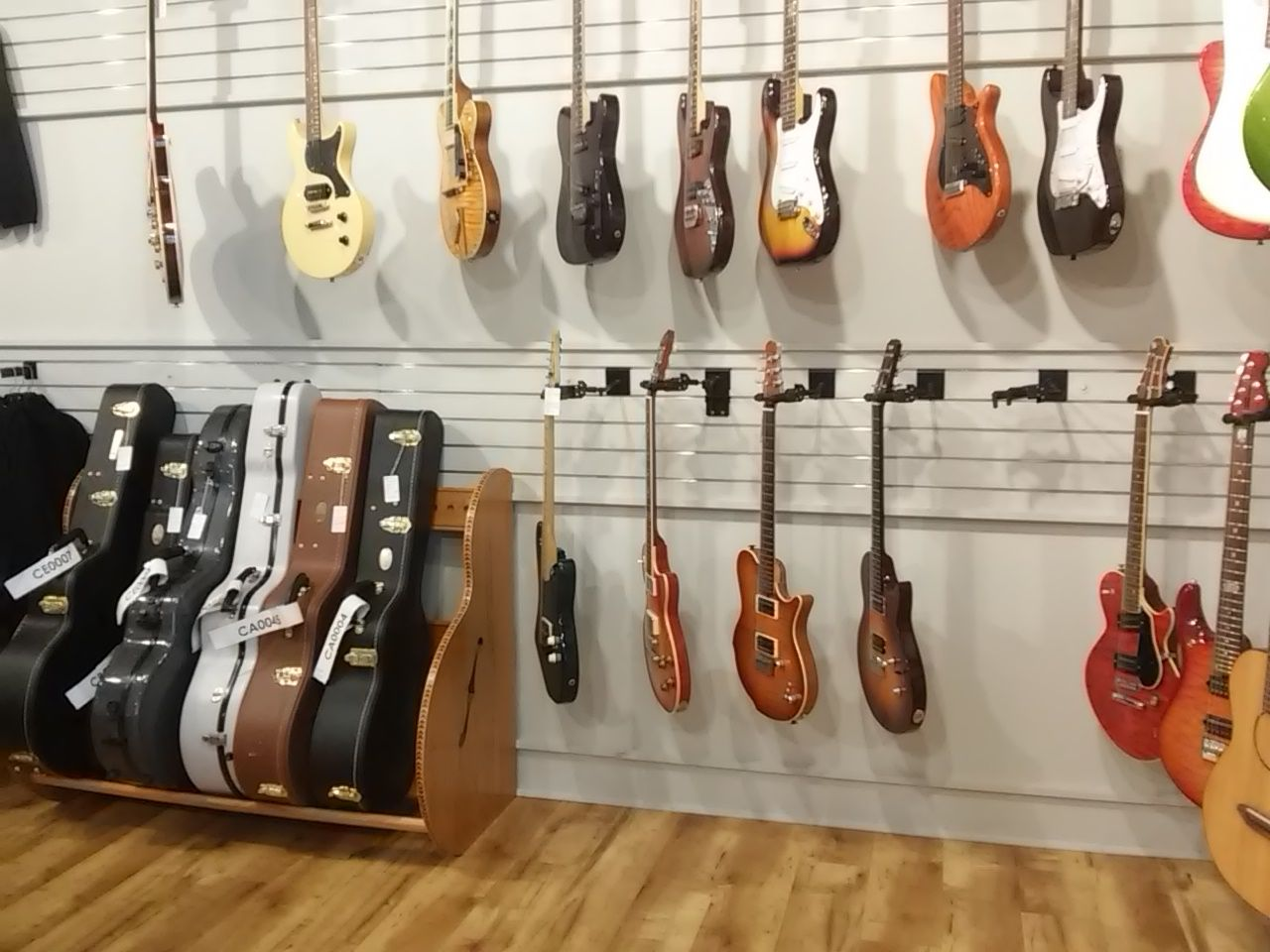 The Studio Guitar Case Storage Rack on display at Gruhn Guitars in Nashville, TN. View details at https://guitarstorage.com/guitar-case-storage-racks/