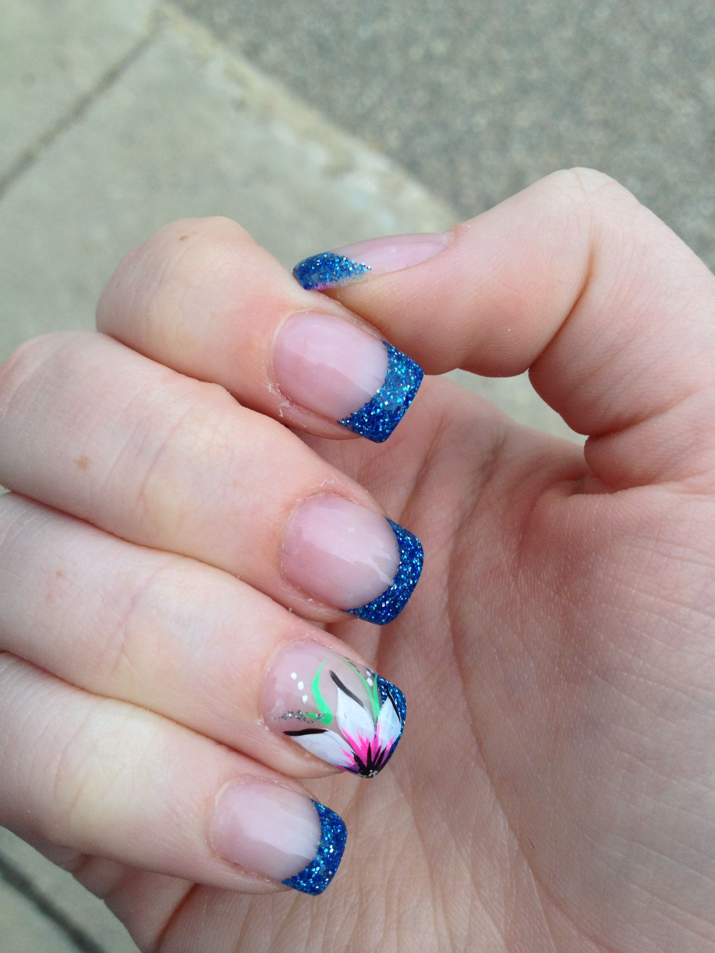 Acrylic nails with a blue sparkle tip and a flower nails