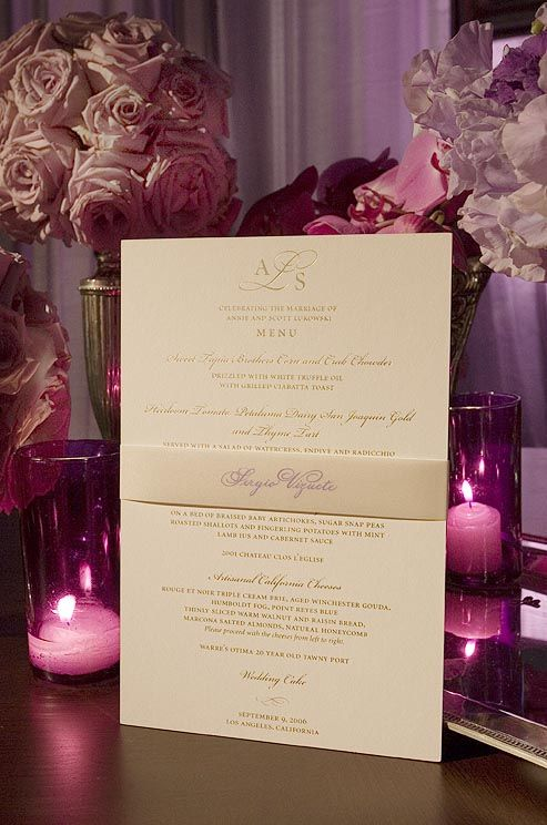 The menu is printed in gold on off-white paper. Each menu is wrapped with a band that serves as a place card. Very elegant!