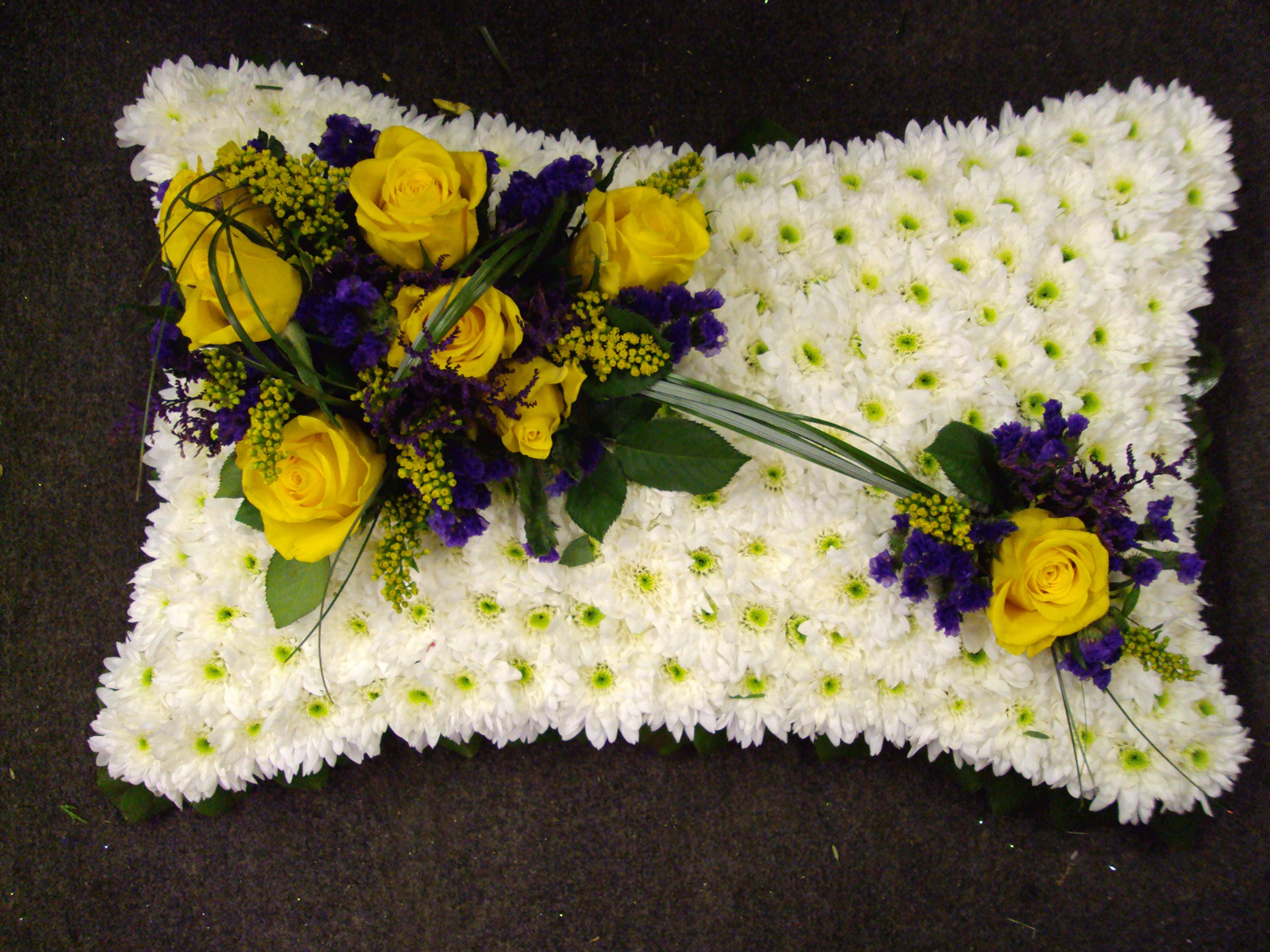 white pillow with yellow rose and purple statice arrangement