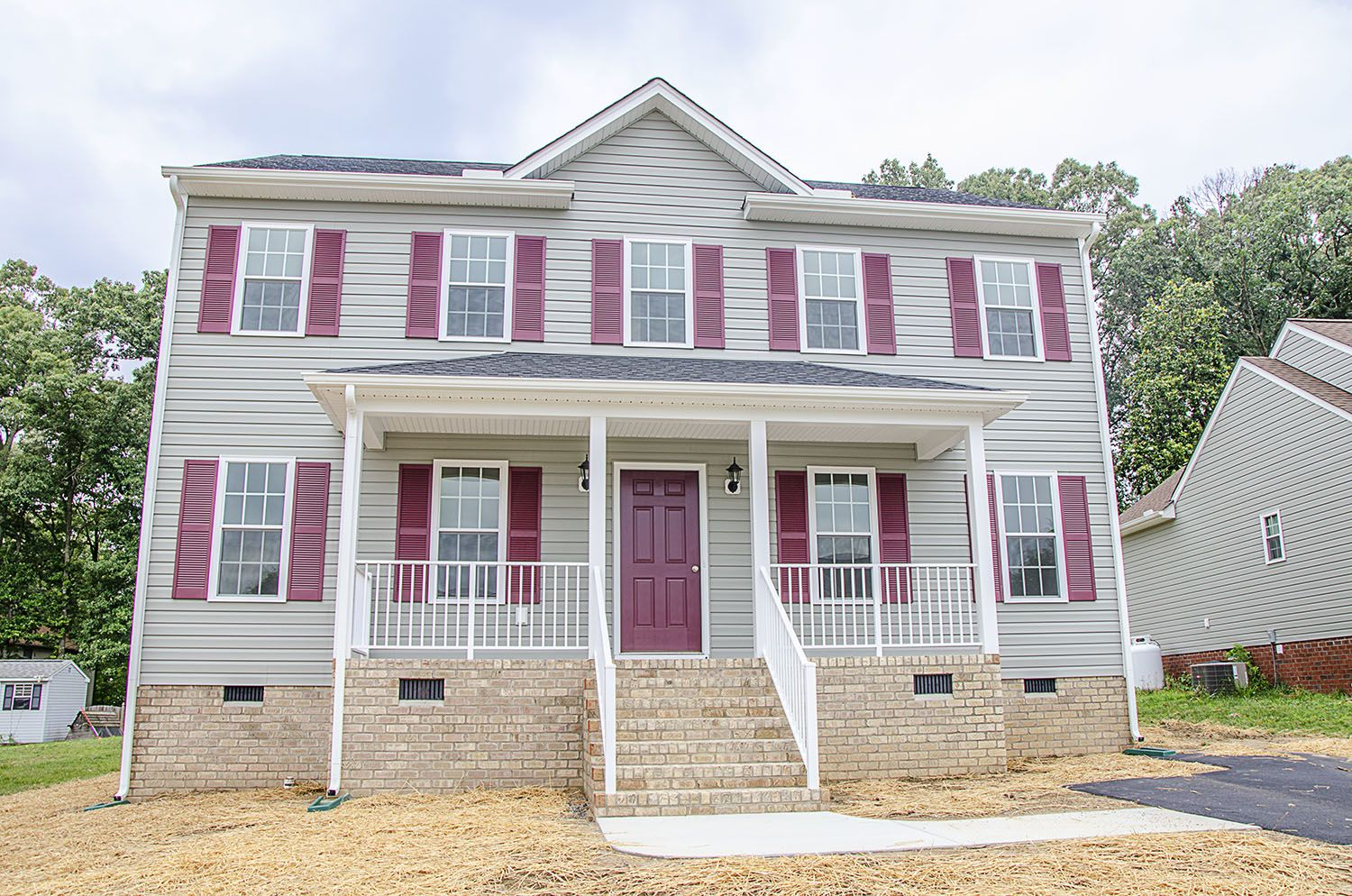 Two Story Home With Gray Siding And Maroon Shutters