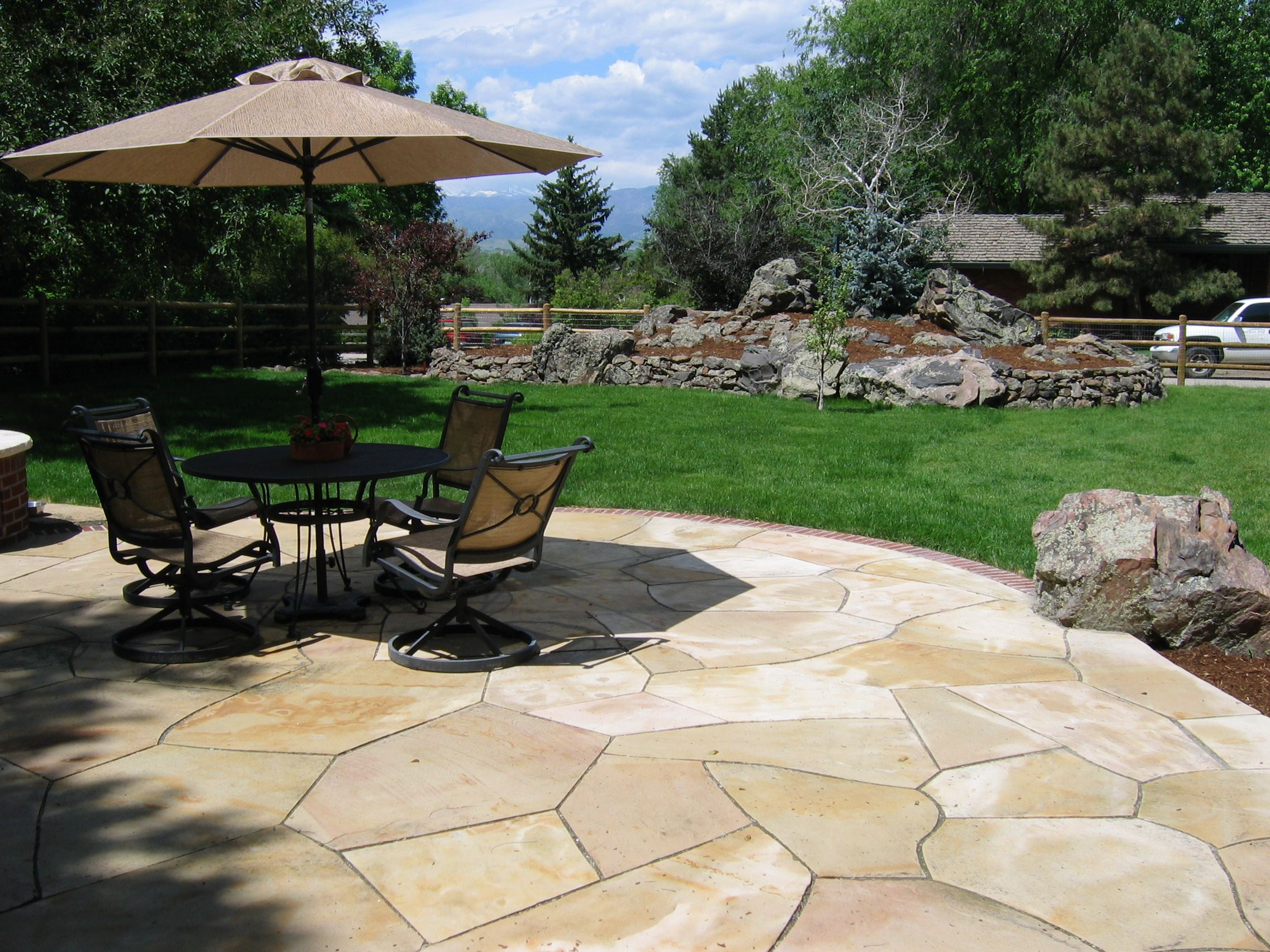 Buff Flagstone Patio With Brick Edger And Natural Boulders By
