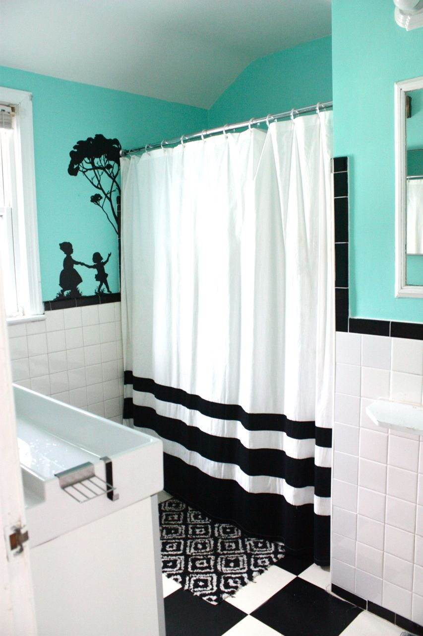 I {{LOVE}} this predominately black and white bath with a beautiful shade of turquoise used on the upper half of the walls, which totally brightens and updates the space.  The awesome decal next to the shower is awesome!  This room is perfection to me!