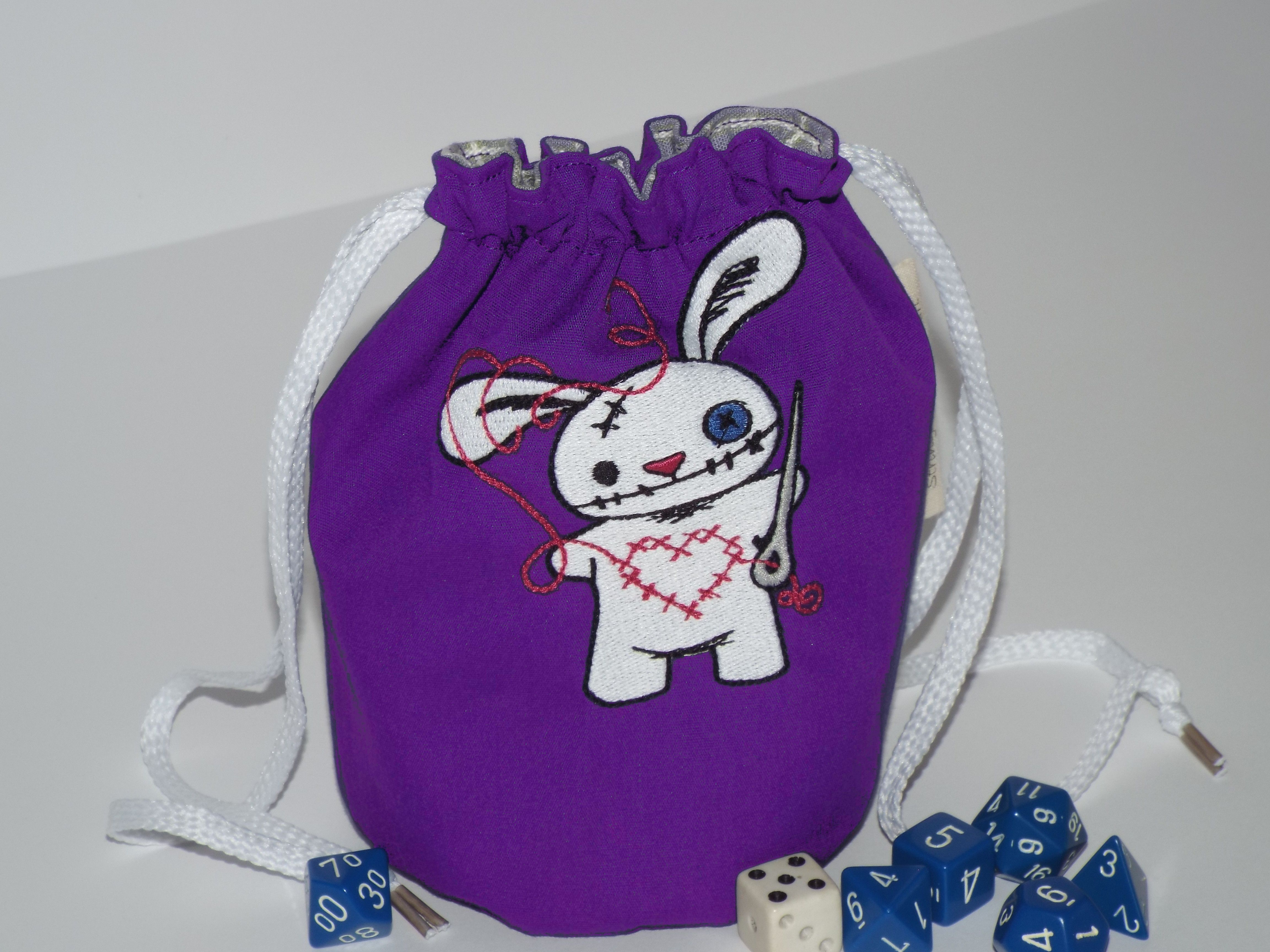 """This purple dice pouch has a machine embroidered white creepy bunny on it. Won't you be his friend? The outer fabric is purple with a purple plaid lining fabric. This pouch is 6 1/2"""" high, 4"""" round. It will stand open on the game table. It has white shoe lace drawstrings on 2 sides. Embroidery pa..."""